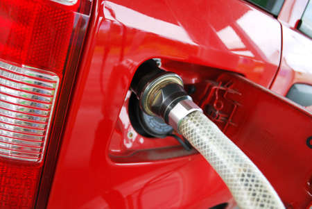 fueling: Ecologic methane red car fueling detail Stock Photo
