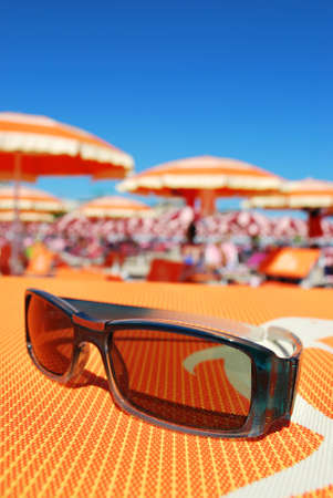 Closeup of sunglasses and beach with orange umbrellas in background, Rimini, Italy