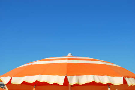 Orange striped beach umbrella over blue sky, free copy space, Rimini, Italy
