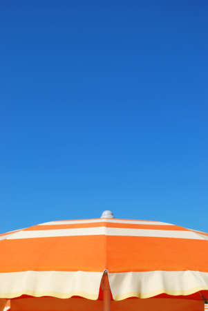 Orange striped beach umbrella over blue sky, free copy space, Rimini, Italy