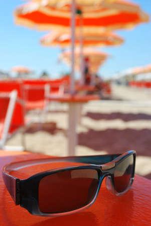 Sunglasses and beach, orange umbrellas in background, Rimini, Italy