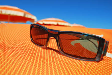 Sunglasses and beach, orange umbrellas in background, Rimini, Italy