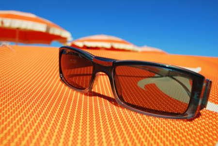 Sunglasses and beach, orange umbrellas in background, Rimini, Italy photo