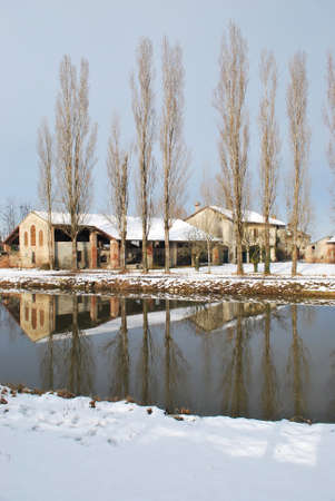 Old country house covered of snow in winter with trees reflecting on the river, Po valley, Italy Stock Photo - 7883300