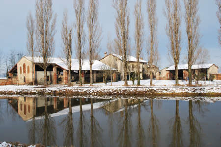 Old country house covered of snow in winter with trees reflecting on the river, Po valley, Italy Stock Photo - 7904834