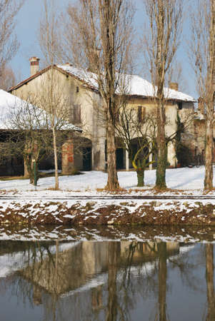 Old country house covered of snow in winter with trees reflecting on the river, Po valley, Italy photo