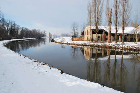 Old country house covered of snow in winter with trees reflecting on the river, Po valley, Italy Stock Photo - 8007991