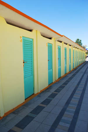 rimini: Perspective row of turquoise and yellow beach huts, Rimini, Italy