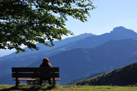 Mujer sentada en un banco en frente de las montañas panorama, Alpes, Piamonte, Italia  Foto de archivo
