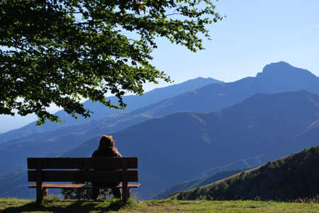 Woman sitting on a bench in front of mountains panorama, Alps, Piedmont, Italy photo