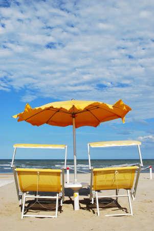 Yellow beach chairs and umbrella, Rimini, Italy Stock Photo - 8212270