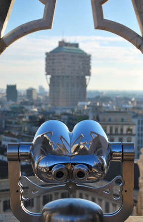 Binoculars telescope looking Milan panorama and Velasca Tower from the roof of the Duomo cathedral, Lombardy, Italy
