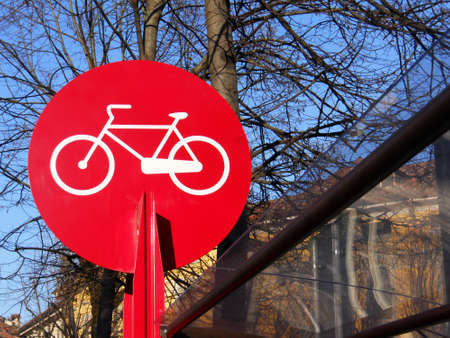 Red and white parking bicycle sign on blue sky and trees photo