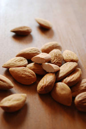 Shelled almonds on natural wooden table background
