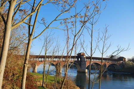 Old covered bridge on Ticino river in Pavia, Lombardy, Italy photo