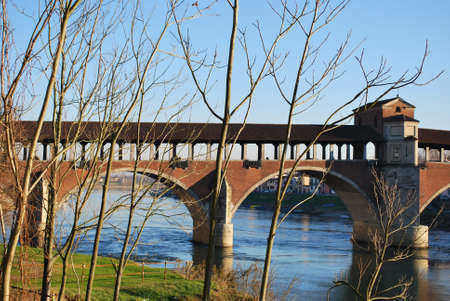 Old covered bridge on Ticino river in Pavia, Lombardy, Italy Stock Photo