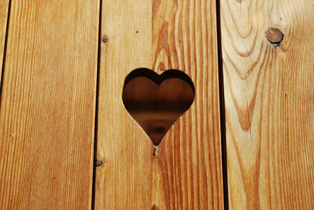 Heart shape hole in a wooden background