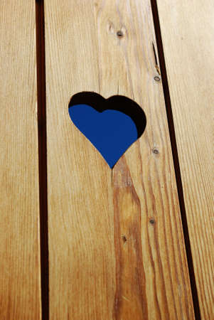 Heart shape hole in a wooden background  photo