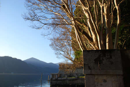 Panoramic view on Orta lake trees and mountains at sunset, Orta St. Giulio, Piedmont, Italy photo