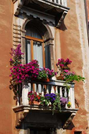 Ancient arched window with balcony and flowers in Venice, Italy photo