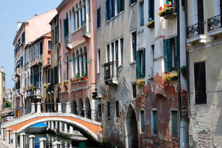 Canal with ancient houses standing in water and bridge in Venice, Italy Stock Photo