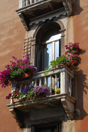 Ancient arched window with balcony and flowers in Venice, Italy Stock Photo
