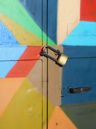 Metal padlock on locked bright colorful door as background photo