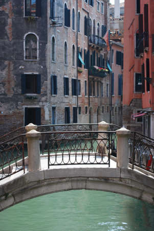 Canal with stone bridge and ancient houses standing in water, Venice, Italy photo
