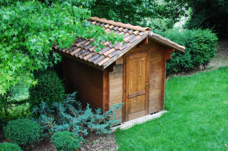 Wooden garden tool shed in a beautiful park photo