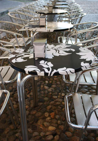 Row of metal chairs and black and white tables in an outdoor bar
