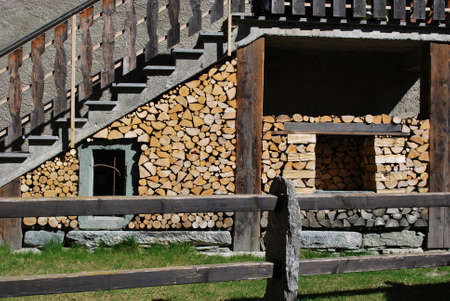 Logs of firewood and typical waltzer wooden chalet on Alps mountains, Alagna village, Piedmont, Italy Stock Photo - 11623140