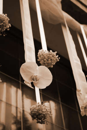 Hanging wedding flowers on the front door of a church, sepia tone