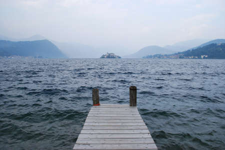 Wooden pier on Orta lake in an autumn day, Orta St  Giulio island and Alps mountains in background, Piedmont, Italy photo