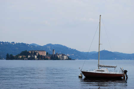 Lonley boat and Orta St  Giulio island on Orta lake, Piedmont, Italy photo