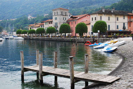 Wooden pier and small Pella village on Orta lake, Piedmont, Italy Stock Photo