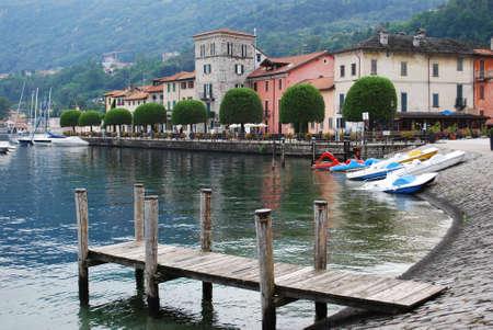 Wooden pier and small Pella village on Orta lake, Piedmont, Italy Stock Photo