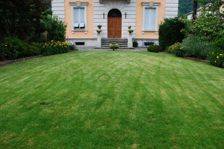 Freshly cut lawn in garden in front of a beautiful ancient villa, Italy Stock Photo