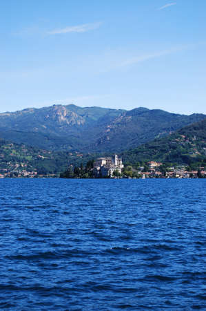 Panoramic view of Orta St  Giulio island on Orta lake in summer with Alps mountains in background, Piedmont, Italy photo