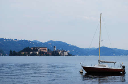 Lonely boat and Orta St  Giulio island on Orta lake, Piedmont, Italy photo