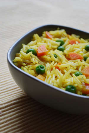 A bowl of yellow basmati rice with carrots, peas, onion and curry photo