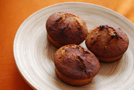 backing: Muffins with hazelnuts, orange peel and raisins in a wooden dish on orange background