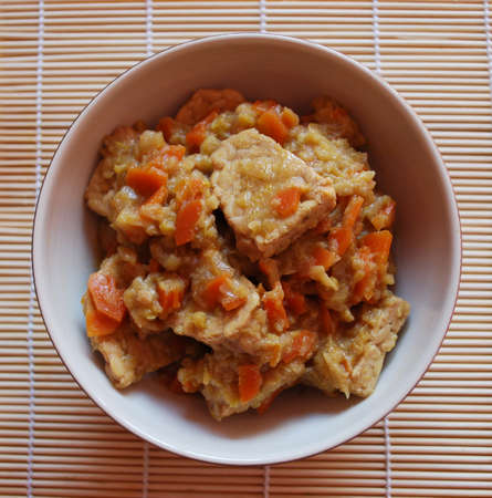 Stew tempeh with carrots, leeks and soy sauce in a bowl Stock Photo
