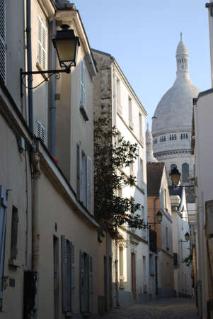 A small alley in Montmartre with the church of Sacre Coeur in background, Paris, France photo