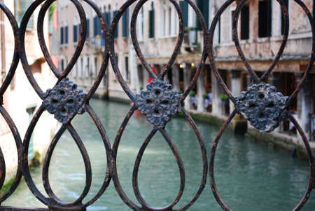 Decorative wrought iron fence of a bridge on a canal, Venice, Italy photo