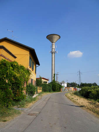 Concrete water tower on clear blue sky in a country road photo