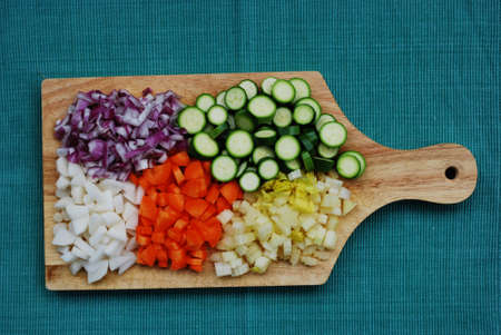 trencher: Colorful vegetables palette on wooden trencher on green background