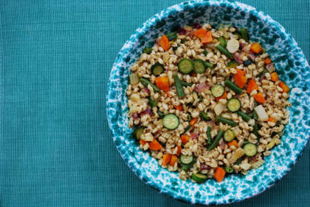 Summer whole barley salad with colorful vegetables in a green bowl photo