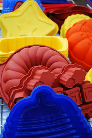 Colorful and differently shaped silicone baking pans as a background photo