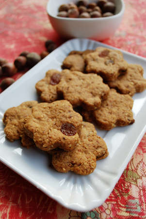 Homemade flower shaped cinnamon cookies with whole wheat, raisins and hazelnuts photo