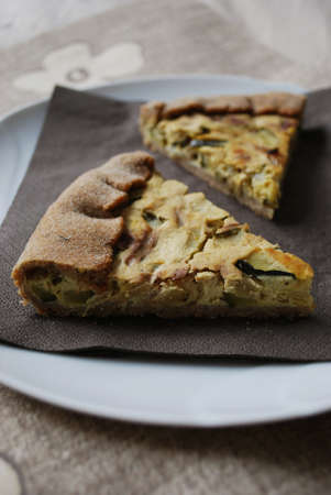 Two slices of vegetarian tart with zucchini, onion and tofu, selective focus Stock Photo